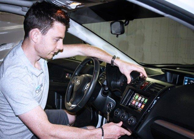 CozyCar team member installing a car stereo system in Kingston, Ontario.
