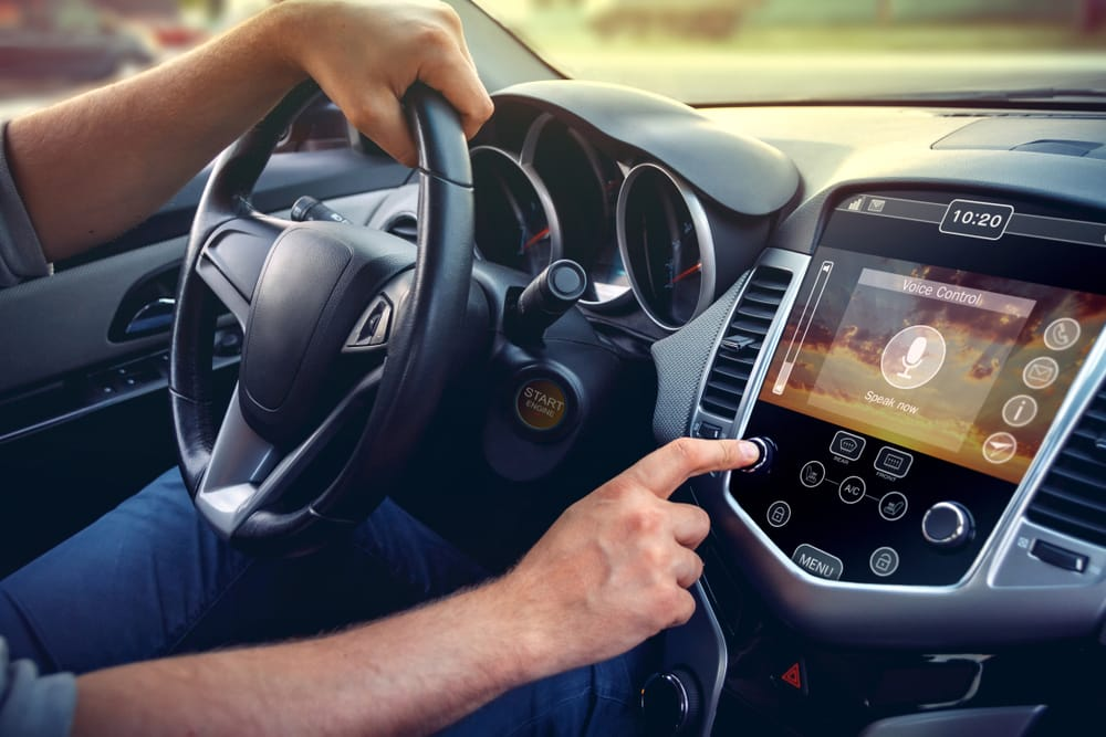 car driver adjusting car stereo