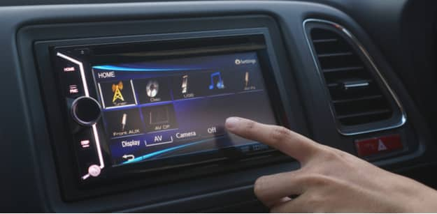 woman touches screen of newly installed car audio system