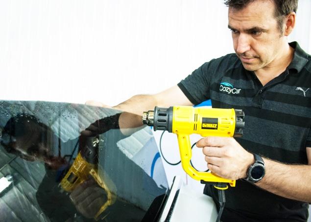 Window Tinting technician applying tint at Kingston's CozyCar